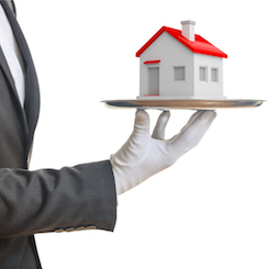 man with white glove holding model of house